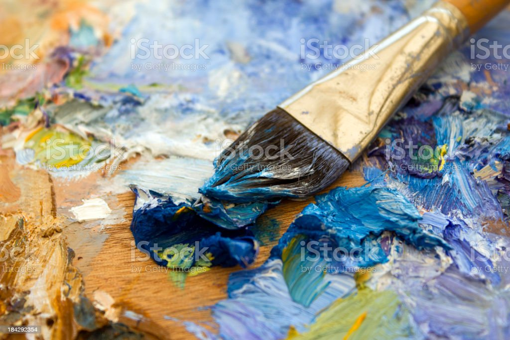 Vibrant multi-coloured artists oil paint palette and brush royalty-free stock photo