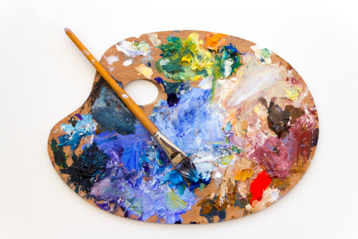 Vibrant multi-coloured artists traditional wooden oil paint palette and brush