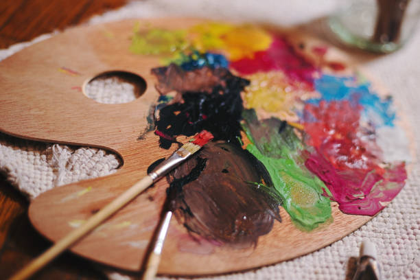 Vibrant Multi Coloured Artists Traditional Wooden Oil Paint Palette And Brush Stock Photo