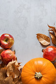 istock Vibrant Orange Color Pumpkin Ripe Organic Red Glossy Apples Pomegranates Chestnuts Dry Autumn Leaves Scattered on Grey Stone Background. Border Frame. Thanksgiving Fall Abundance. Copy Space 867472720