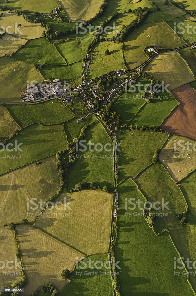 Vibrant patchwork landscape village summer fields royalty-free stock photo