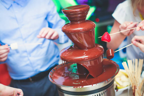 Vibrant Picture of Chocolate Fountain Fontain on childen kids birthday party Vibrant Picture of Chocolate Fountain Fontain on childen kids birthday party chocolate fondue stock pictures, royalty-free photos & images