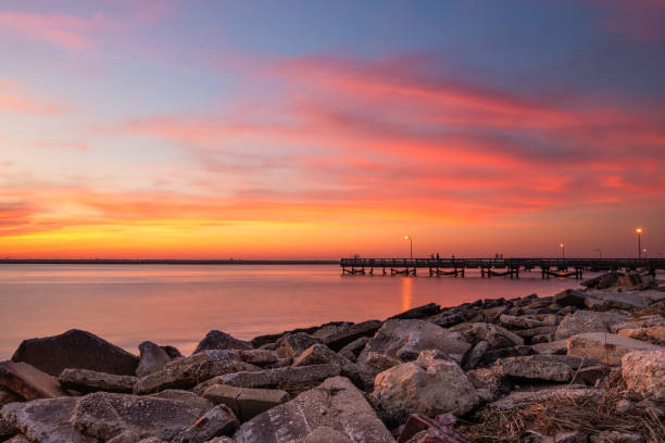 Vibrant pink and orange sunset over a fishing pier and rock jetty.