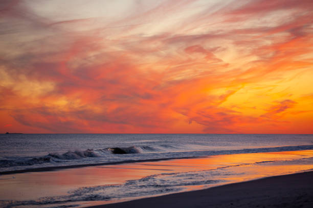 Vibrant pink and orange sunset over small waves breaking on the beach.