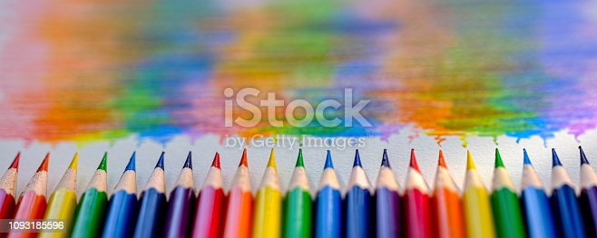 Vibrant rainbow colored coloring pencils or crayons in a row laying vertically with corresponding colorful rainbow shade drawing background, of the colors bending together, which features behind the crayons. Concept image of people living together in harmony, mixing together, peace etc.