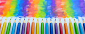 Vibrant rainbow colored water color coloring pencils or crayons in a row lying vertically with corresponding colorful shade drawing background, of the colors blending together, which features behind the crayons.. Concept image of people living together in harmony, mixing together, peace etc.