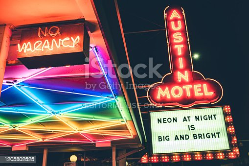 Austin, Texas, USA- February 3, 2020. Colorful neon and murals scenes in the evening on Historic Rainy street Historic District in Austin, capital city of state f Texas in USA. Variety of restaurants, stores and businesses at the street front. Motel sign  on city corner.