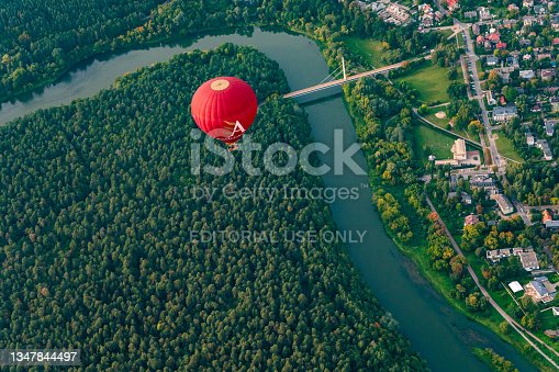 istock Vibrant red hot air balloon flying above Vilnius capital of Lithuania. Neris river flowing curve through the city. Zverynas district and Vingis park surrounded by river paths. 1347844497