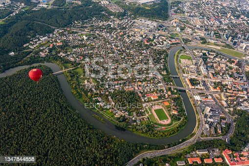 istock Vibrant red hot air balloon flying above Vilnius capital of Lithuania. Neris river flowing curve through the city. Zverynas district surrounded by Neris river. Cityscape views from the sky 1347844858