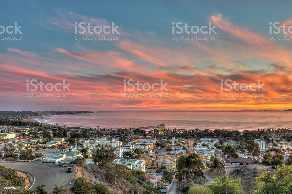 Vibrant sky over small, coastal town. stock photo