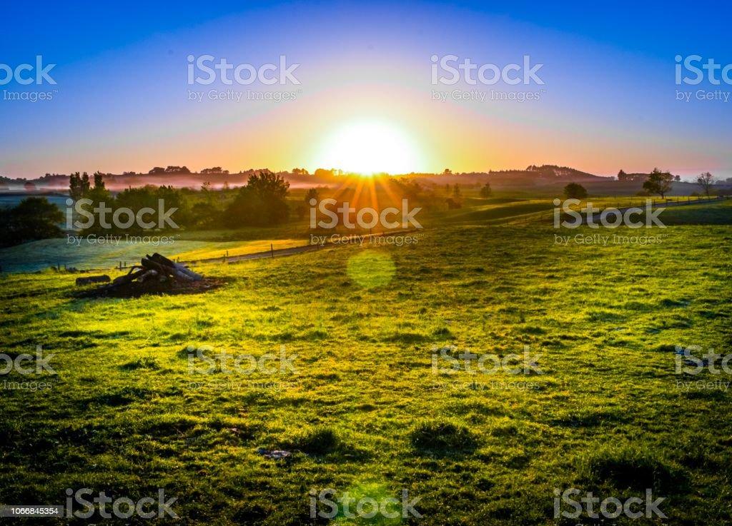 Vibrant sunrise on a farm in rural New Zealand stock photo