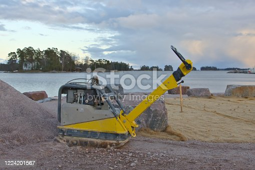 Vibratory plate compactor under construction on seashore for making new public park, Finland.
