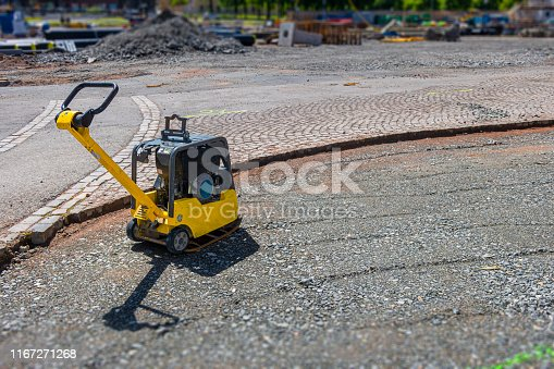 Vibratory plate compactor in a construction site