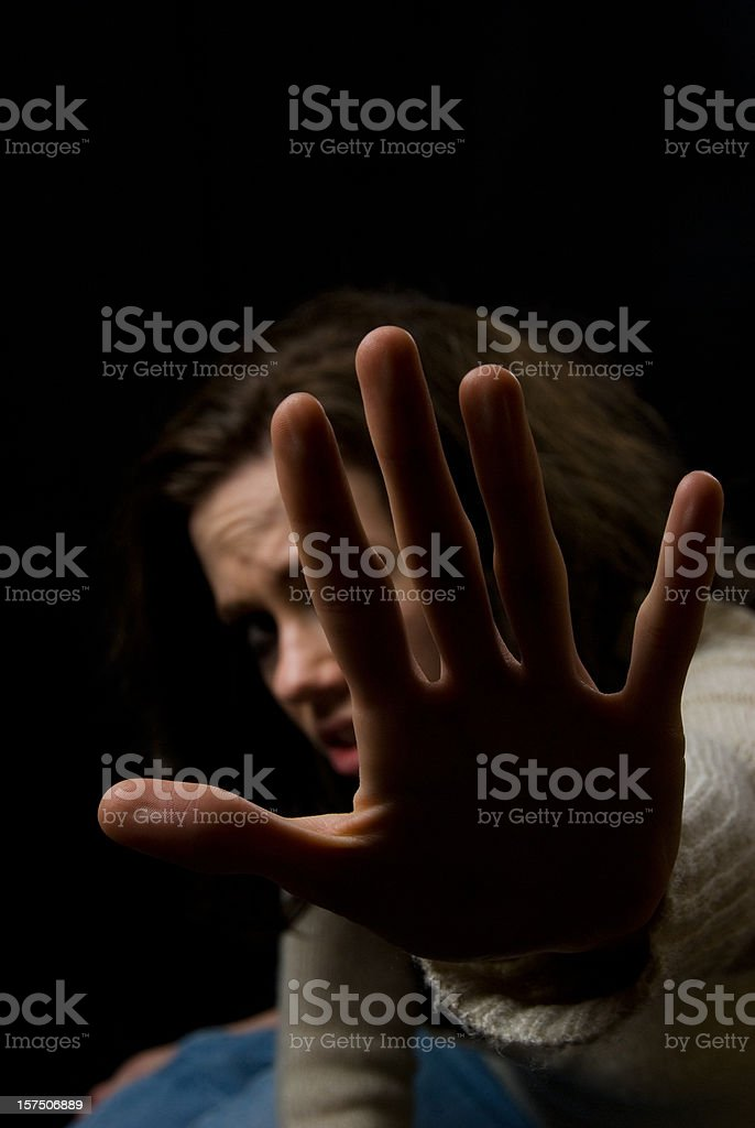 Victim concept: scared woman protecting herself royalty-free stock photo