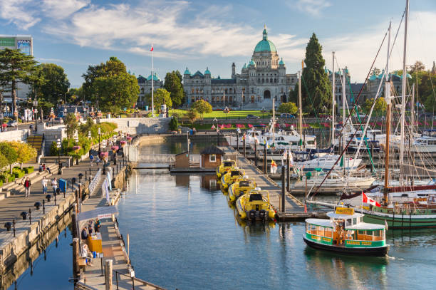 Victoria Harbour and British Columbia Parliament Buildings at sunset Victoria, British Columbia, Canada - 11 September 2017: Victoria Harbour and British Columbia Parliament Buildings at sunset british columbia stock pictures, royalty-free photos & images