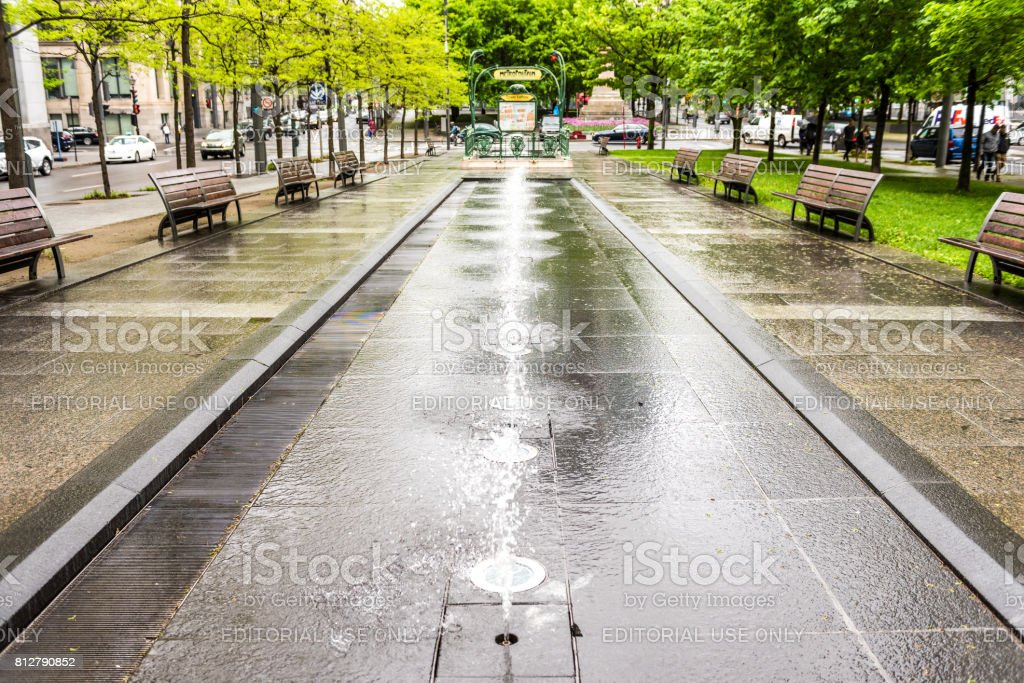 Victoria Square Metro station park with fountains during rainy cloudy day in city in Quebec region stock photo
