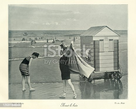 Antique photograph, Victorian Bathing machine, women in swimwear, seaside, 19th Century. The bathing machine was a device, popular from the 18th century until the early 20th century, to allow people to change out of their usual clothes, change into swimwear, and wade in the ocean at beaches. Bathing machines were roofed and walled wooden carts rolled into the sea.