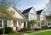 Belmont, North Carolina, USA - April 17, 2013: The American Dream is pictured in this iconic image of a row of new, Victorian-style homes in the Eagle Park neighborhood development. Most American homes are now built on smaller lots with sidewalks and tree-lined streets in the suburbs of large cities. Image adds focus to the American Flag hanging from the porch.