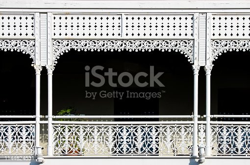 Victorian decorative wrought iron balcony with a plant on it but mostly darkness behind the white painted ornate railings - background