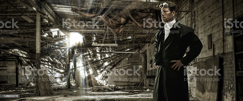 Victorian Era Man Standing in Abandoned Warehouse stock photo