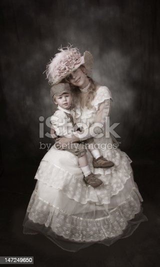 Victorian era mother and son posing with victorian tea hat, dress, and boy in newsboy knickers and cap