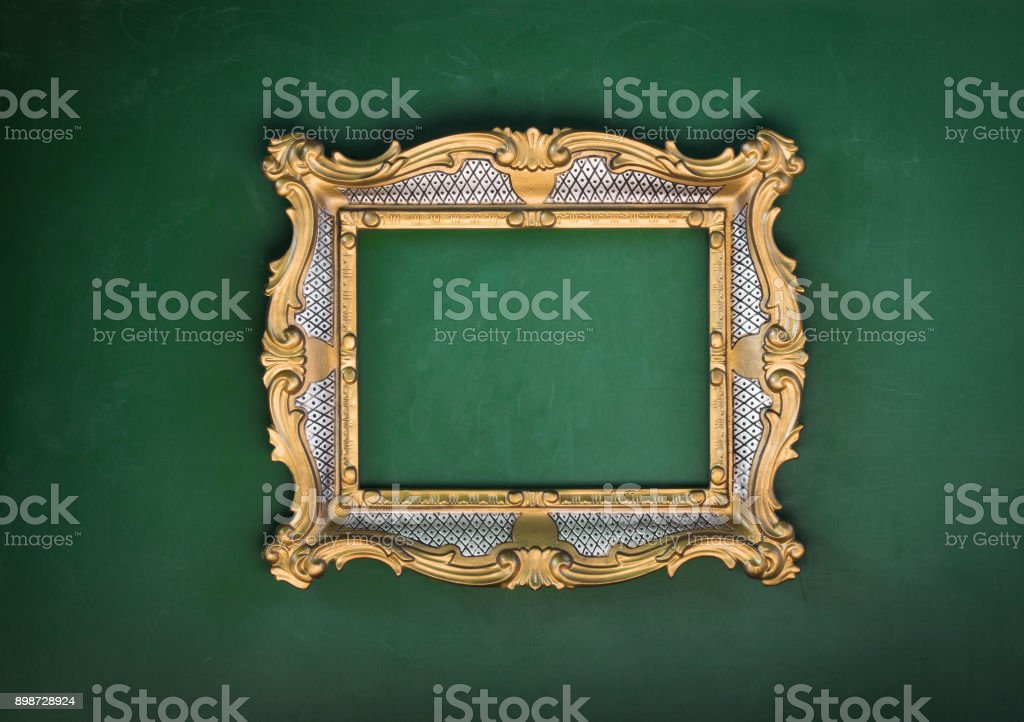 victorian golden baroque frame on a green background stock photo