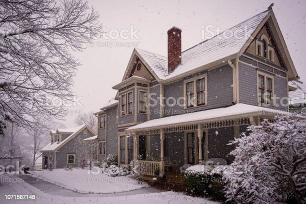 Photo of Victorian House During Snowstorm.