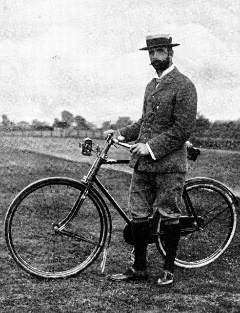 Victorian image of a man in plus fours and a boater stood besides his bike; from The Navy and Army Illustrated 1899 Taken from the Navy and Army Illustrated annual of 1899 19th century stock pictures, royalty-free photos & images
