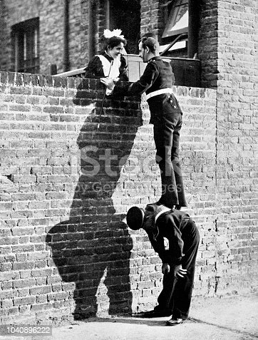 istock Victorian image of a soldier stood atop a sailors back so he can talk to a pretty lady atop a tall brick wall; 19th century humour ; from The Navy and Army Illustrated 1899 1040896222