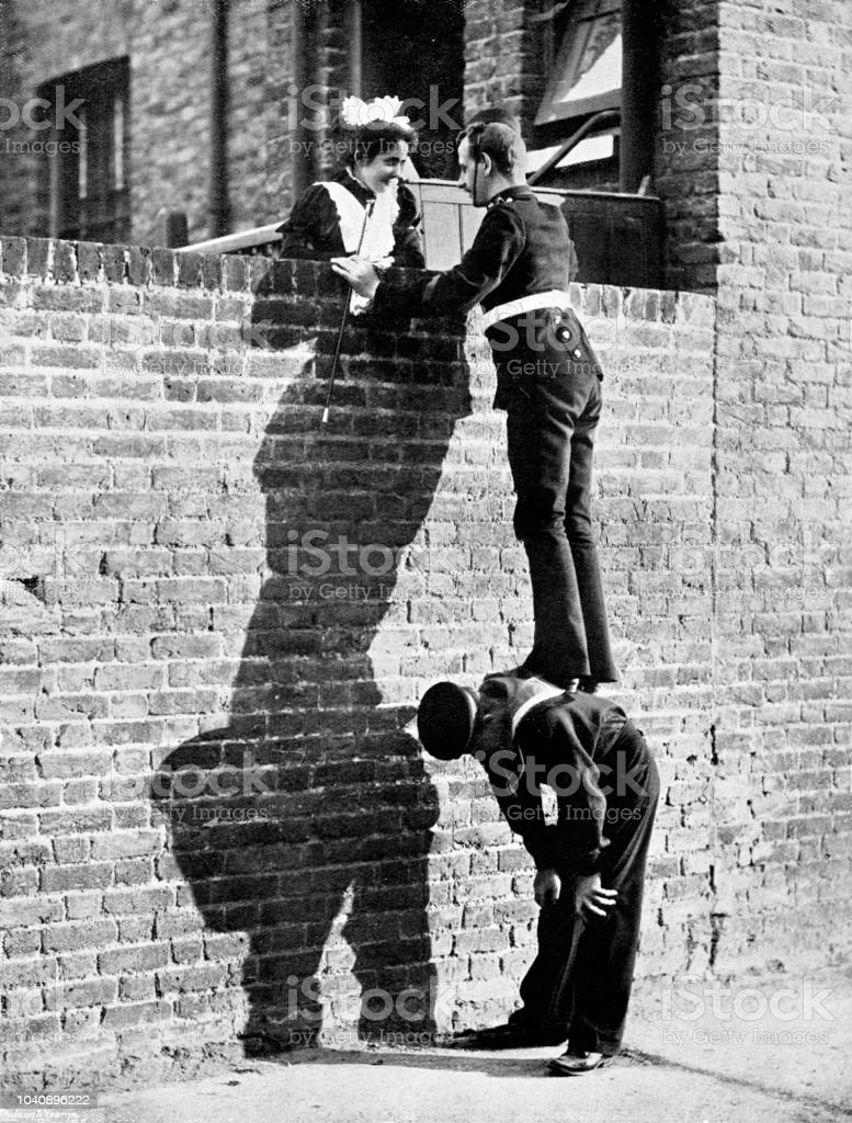 Victorian image of a soldier stood atop a sailors back so he can talk to a pretty lady atop a tall brick wall; 19th century humour ; from The Navy and Army Illustrated 1899 stock photo