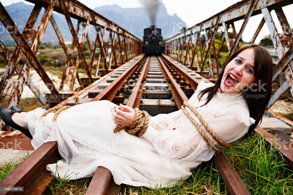 Victorian melodrama: steam train nears woman tied to railroad tracks stock photo
