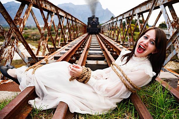 victorian melodrama: trem a vapor s'aproxima de sua mulher relacionados aos trilhos da estrada de ferro - amarrado - fotografias e filmes do acervo