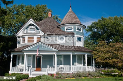 Beautiful gray traditional victorian house.  House has an American Flag haning over the porch and shows a beautiful garden with flowers and trees.  Set against a cloudless blue sky