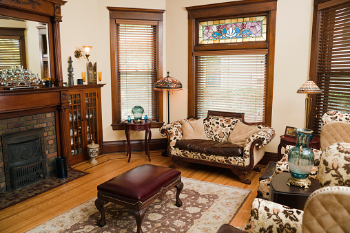 Victorian style living room, an old-fashioned, domestic residential home interior. The interior room of a renovated and restored house with antique furniture and accessories. Classic, traditional furnishings define the space, in a horizontal format with no people.