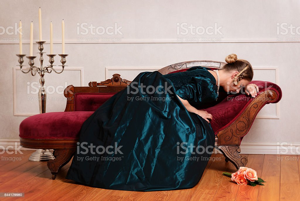 victorian woman crying on couch stock photo