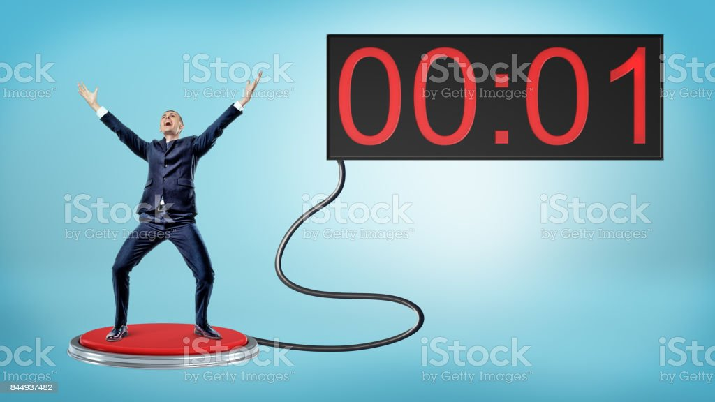 A victorious businessman on a large red push button connected to a screen with one remaining second stock photo