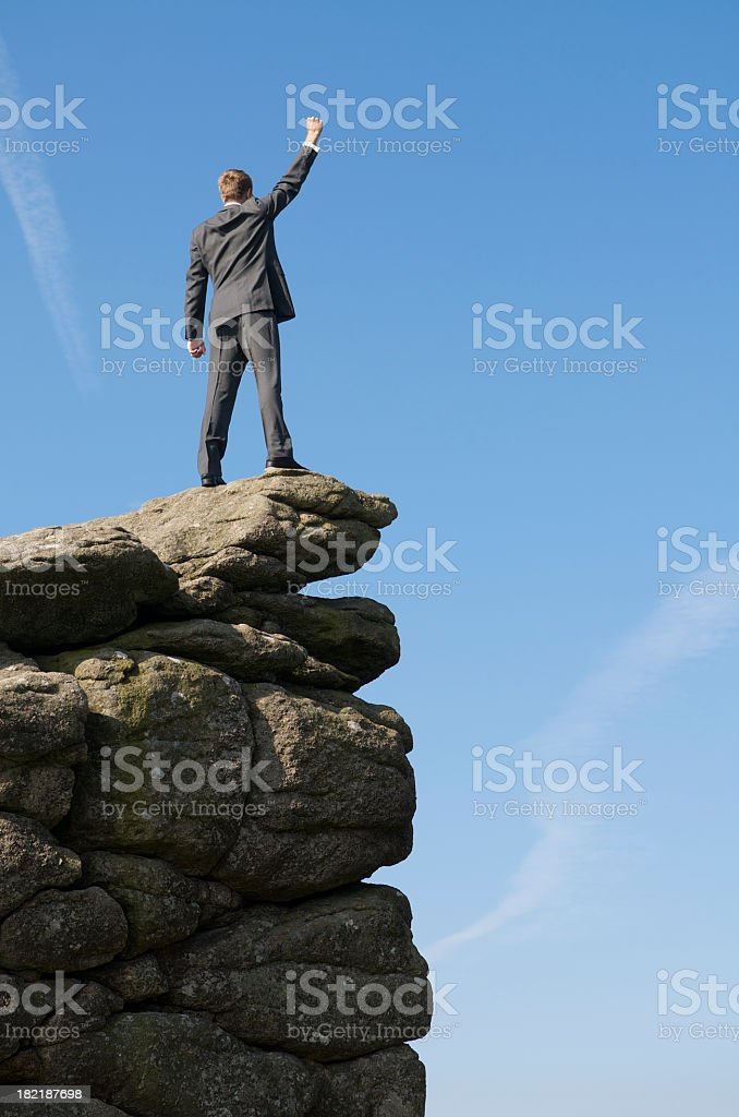 Victorious Businessman Standing Outdoors on Mountaintop stock photo
