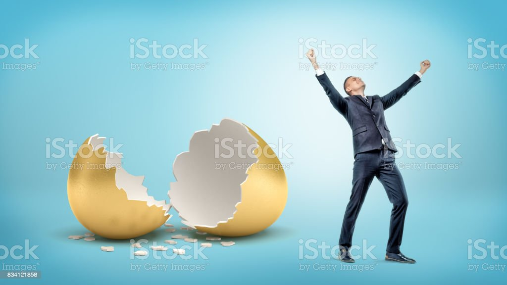 A victorious businessman stands near a large broken golden eggshell on blue background stock photo