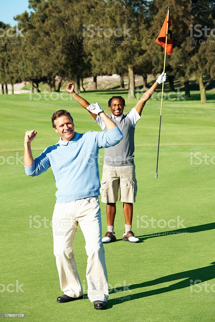 Victorious golfer with a friend at the back royalty-free stock photo