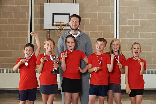 Victorieux école équipe sportive avec médailles trophée et dans la salle de sport - Photo