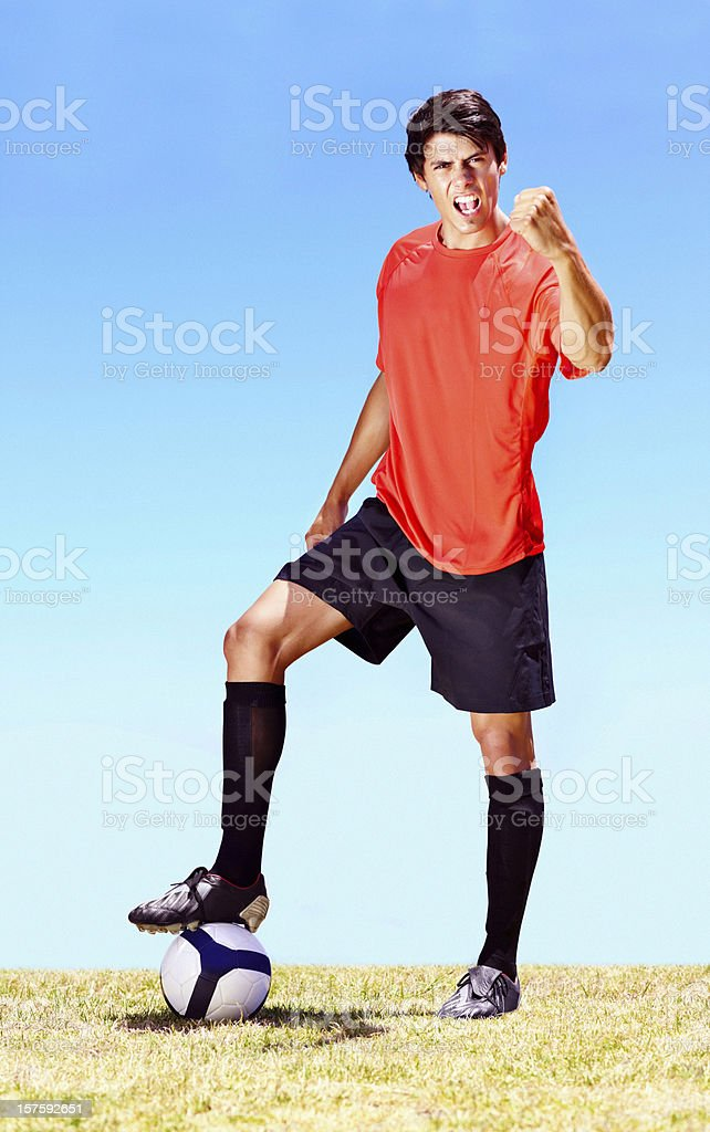 Victorious soccer player with a football on the field royalty-free stock photo