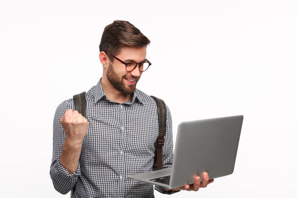 Victorious student surfing laptop on white Young student in glasses with backpack holding laptop and celebrating victory isolated on white. laptop white background stock pictures, royalty-free photos & images