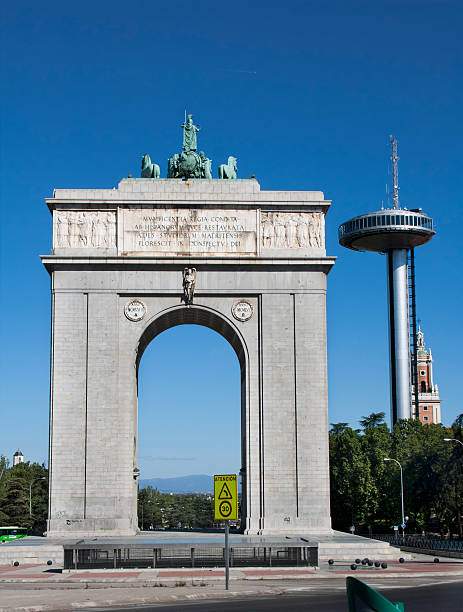 Victory arch and Faro de Moncloa. Memorial arch and, in the background, transmission, communications tower and observation point. civil war memorial minnesota stock pictures, royalty-free photos & images