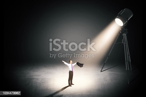 business victory concept with cheerful businessman with arms up under spotlight at dark background