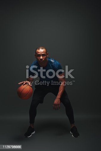 Full length portrait of basketball player standing over dark background with a ball in his hand. He is ready to play the game