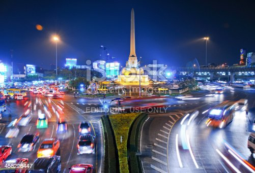 Bangkok, Thailand -February 5, 2011: The usual busy traffic rolling by Victory monument (Anusawari Chai Samoraphum in thai), a statue erected in 1941 to commemorate Thailands victory in the Thai-Franco war.