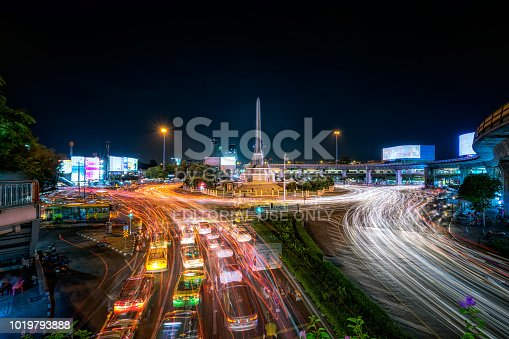 Victory Monument is an Obelisk monument in Bangkok, Thailand. Beautiful city night scenery photography. Heavy traffic in downtown Bangkok, Thailand.