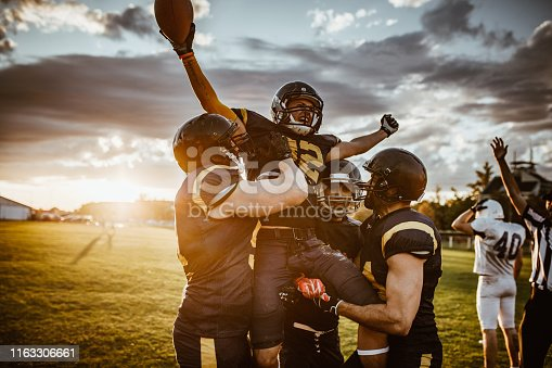 Team of American football players celebrating victory at sunset.