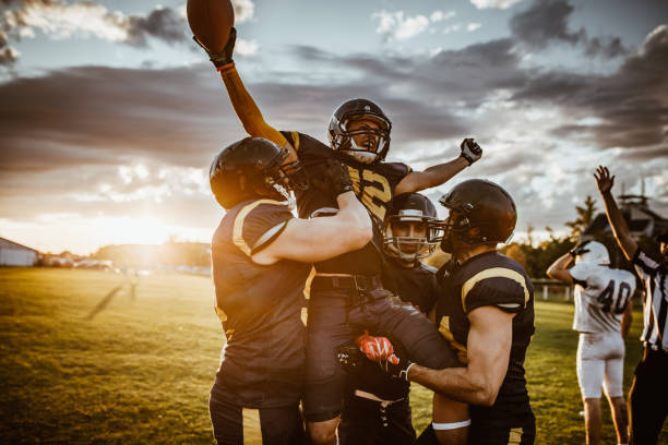 Victory on American football match! Team of American football players celebrating victory at sunset. win stock pictures, royalty-free photos & images