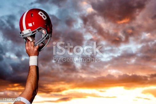 An American football player raises his helmet in victory.